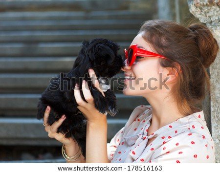 Young brunette woman hugging her lap dog puppy. Retro style - stock photo