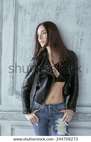 young brunette woman in leather jacket at vintage wall, old interior - stock photo