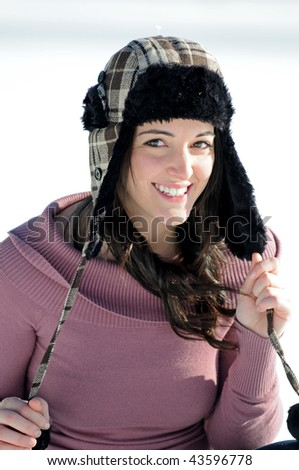 Young brunette woman in sweater and fur lined hat walking in snow - stock photo