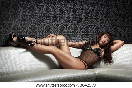 Young brunette woman on the sofa - stock photo