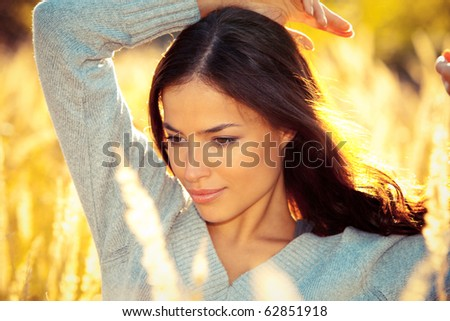 young brunette woman  portrait at sunny yellow autumn field - stock photo