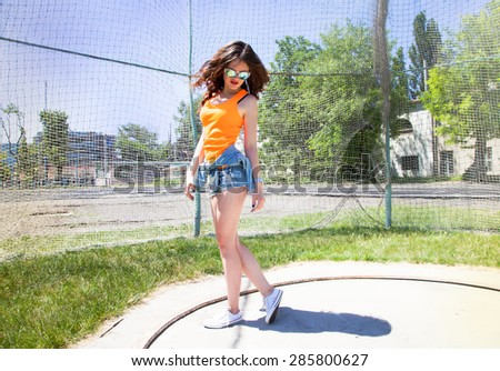 Young brunette woman posing at the stadium,mirrored sunglasses and bright make up,show emotions.Lifestyle portrait bright toned colors.Portrait of a beautiful and fashionable,professional hair style - stock photo