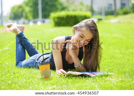 Young brunette woman reading magazine lying on green grass - stock photo
