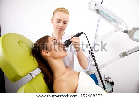 Young brunette woman receiving laser therapy. Spa studio shot - stock photo