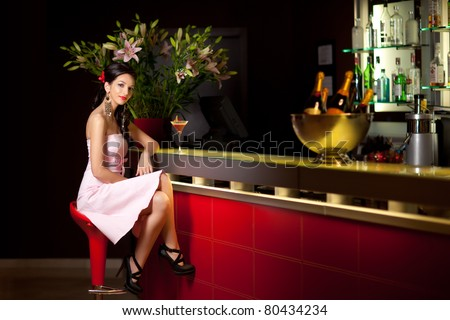 young brunette woman sitting at the bar - stock photo