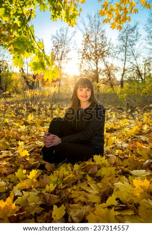 Young brunette woman sitting on grass at autumn park at sunny day - stock photo