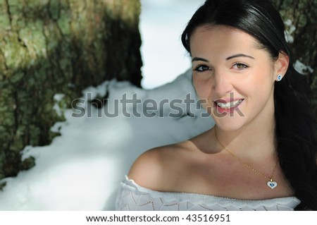 Young brunette woman standing outside next to snowy tree - stock photo