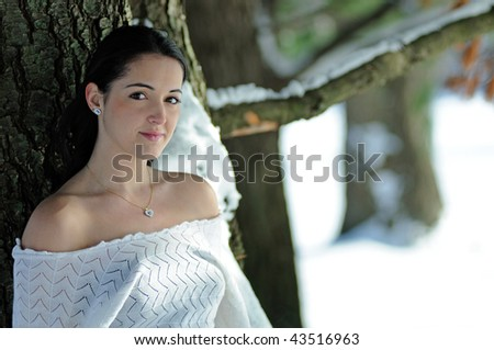 Young brunette woman standing outside next to snowy tree - shade - stock photo