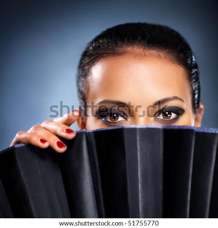Young brunette woman stranger portrait. On blue background. - stock photo