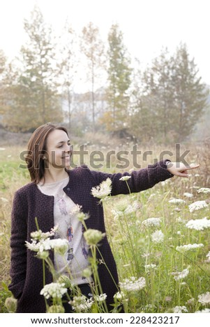 young brunette woman with coat indicating the nature on wildflowers field in the countryside with soft  sunlight - stock photo