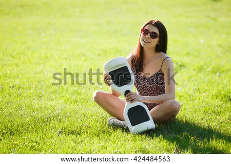 Young brunette woman with electrical mini hover board scooter in green park. Good summer weather, trendy transportation technology and cute model.  - stock photo
