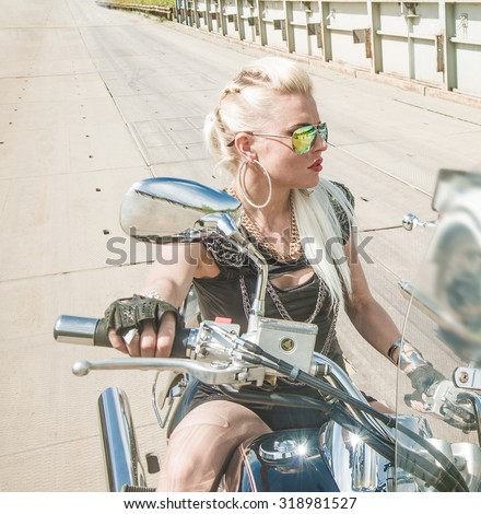 Young brutal cute girl lie on chopper and wear black leather dress and stylish sunglasses Empty space for inscription Biker Woman on motorcycle against metal bridge background Blond female - stock photo