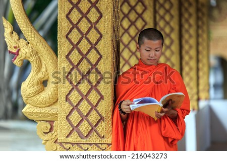 Young Buddhist Monk Reading Prayer Book in Laos temple - stock photo
