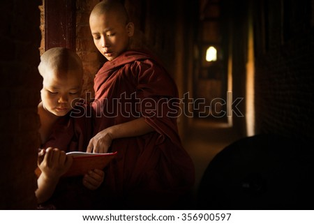 Young Buddhist novice monk reading in monastery with beautiful natural sunlight from window. Buddhist teaching, Myanmar. - stock photo