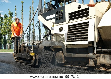 Young builder and Asphalt spreader during Road street repairing works - stock photo