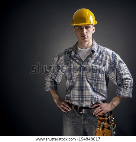 Young builder on a black background - stock photo