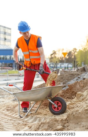 Young building worker loading a wheelbarrow - stock photo