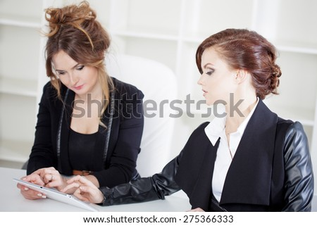Young buisnesswoman showing something to her colleague, on the laptop.  - stock photo