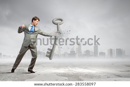 Young businesman crashing stone key with fist punch - stock photo