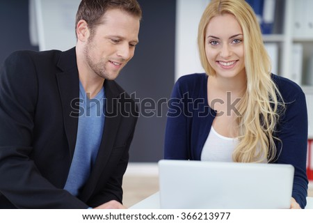 Young business colleagues working as a team sitting together at a desk sharing a laptop computer with focus to a smiling friendly woman - stock photo