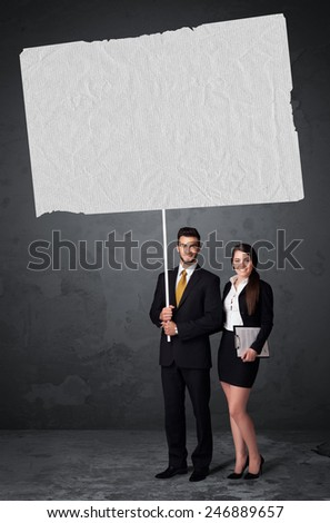 Young business couple holding a big blank booklet paper  - stock photo