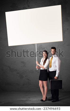 Young business couple holding a blank whiteboard - stock photo