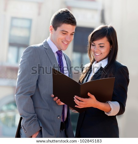 Young Business couple looking at file outdoors. - stock photo