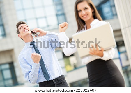 Young business couple standing in front of office buildings caught in the moment of joy for the successful completion of the job. - stock photo
