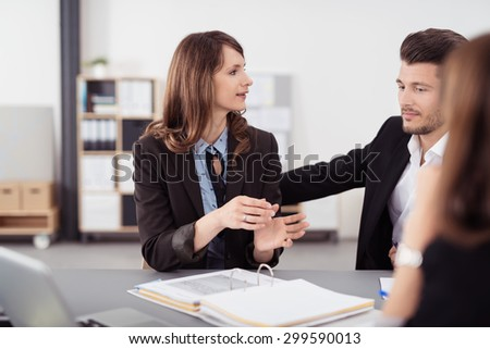 Young Business Couple Talking to a Financial Agent at the Table with Contract Ready Inside the Office. - stock photo