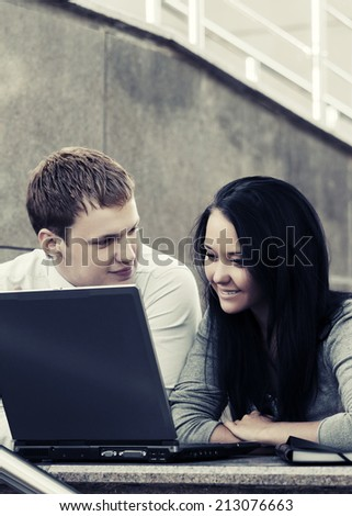 Young business couple using laptop outdoor - stock photo