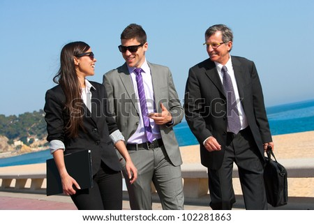 Young business couple walking with colleague outdoors. - stock photo