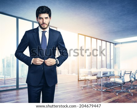Young business man and sunny office interior - stock photo