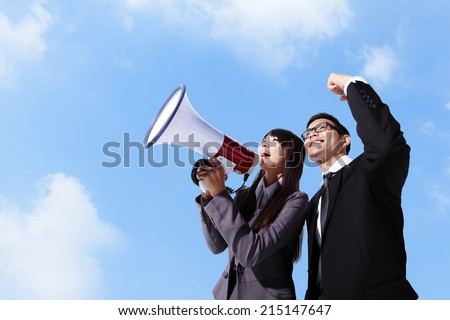 Young business man and woman shouting into a megaphone up forward with sky background, asian - stock photo