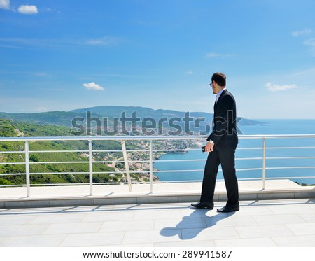 Young business man calling by cell phone on white beach - stock photo