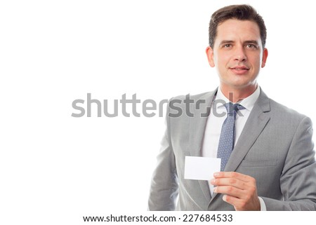 Young business man close up over white background. Showing a white business card - stock photo