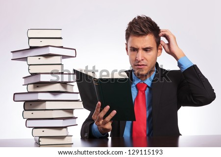 young business man confused of what he is reading at his desk - stock photo