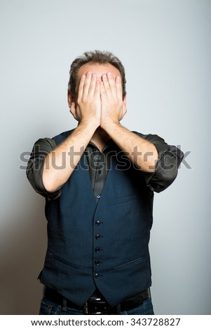young business man covers his face, manager, office style studio shot isolated on the gray background - stock photo