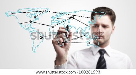 Young business man drawing a global network or globalization concept on world map.  Man drawing internet diagram or business connection on a glass window. On a gray background. - stock photo
