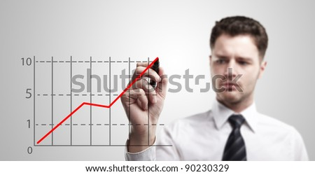 Young business man drawing a graph on a glass window in an office - focus is on graph. Businessman drawing a rising arrow, representing business growth. - stock photo