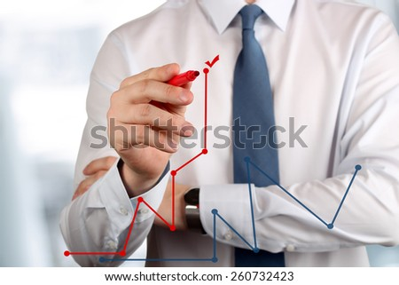 Young business man drawing  a graphs by red pen  - stock photo