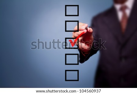 Young business man drawing a tick on a glass window in an office. Man choosing one of three options. On a gray background - stock photo