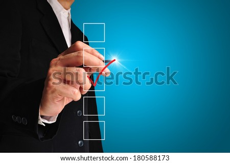 Young business man drawing a tick on touch screen - stock photo