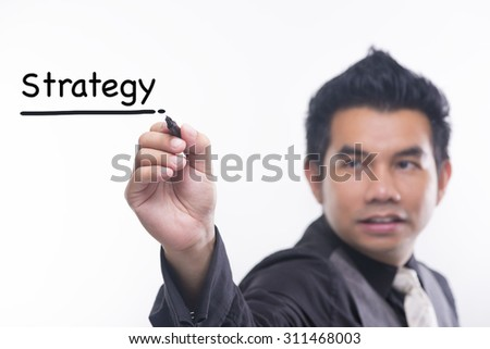 Young business man draws a word strategy - stock photo