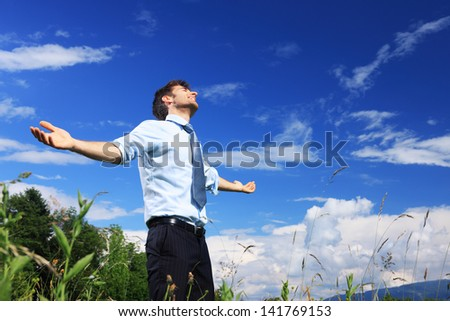 Young business man enjoying the fresh air on a sunny day - stock photo
