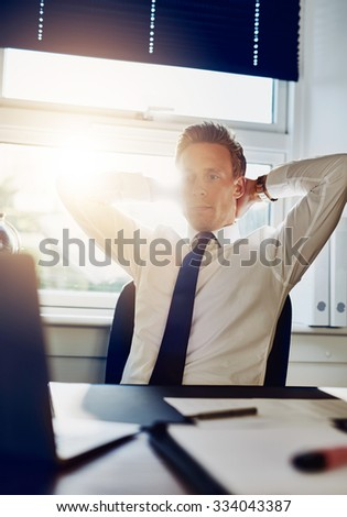 Young business man entrepreneur working overtime at his office looking at his computer with arms behind his neck - stock photo