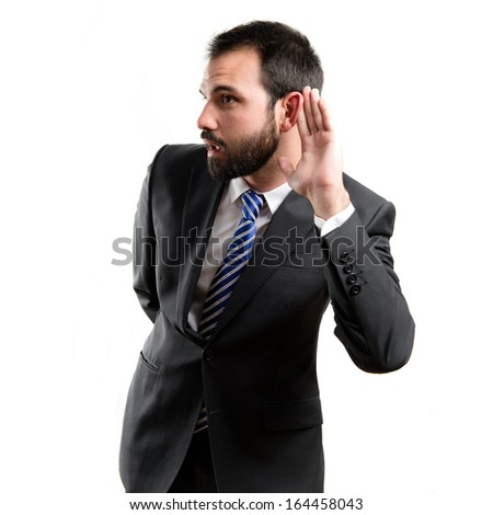 Young business man hearing something over white background  - stock photo