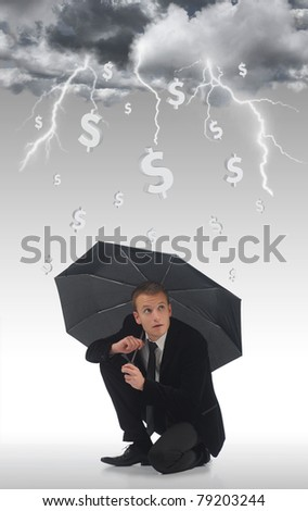 Young business man holding an umbrella under a storm of money - stock photo
