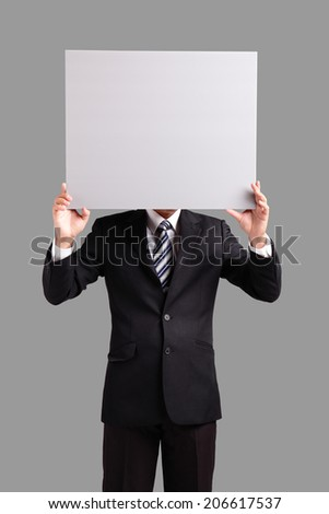 Young business man holding blank billboard card on his face with copy space isolated on gray background - stock photo