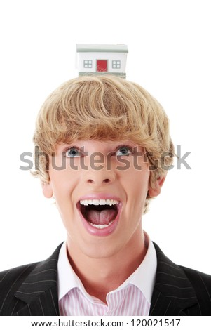 Young business man holding house model on his head - real estate concept. - stock photo