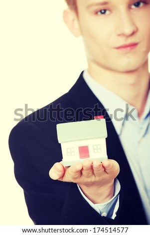 Young business man holding house model - real estate concept. Isolated on white  - stock photo